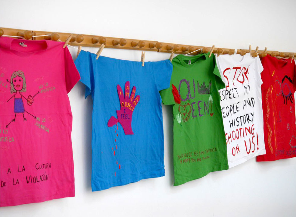 "Twenty-four cotton T-shirts in different colors with handmade messages in English and Spanish about gender violence. For example, one has the phrase ""Healing is not a linear process"" written on it, below six feathers. Another one is torn, simulating an eye, and has phrases about rape connected with arrows (""Shhh; you are a woman now; boys will be boys, can't you just get over it?; Don't tell""). Another one has a pink hand pasted on, with the thumb cut and bleeding. Inside the hand, the message written is ""I am not an object, I feel""."