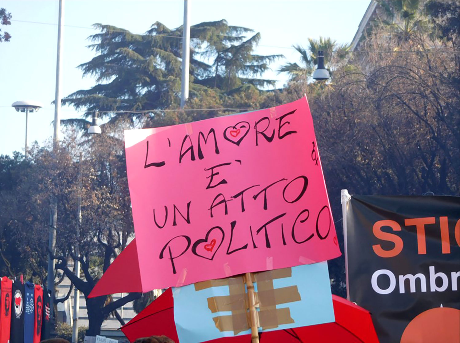 Picture of a protest banner. Black marker on pink background. Spelling the words 'L'amore è un gesto politico' ['Love is a political gesture'].
